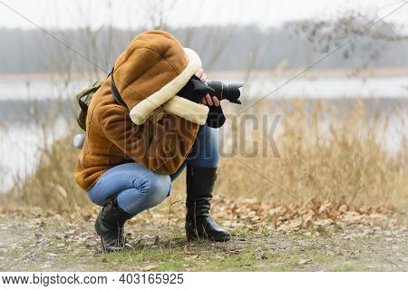 Girl Photographer With A Camera. Woman Tourist, Blogger, Photographing Nature. Autumn Background. Co