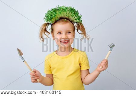 The Child Is Happy With The Sprouts Of Fresh Greens. The Girl Holds A Shovel And Rake In Her Hands A