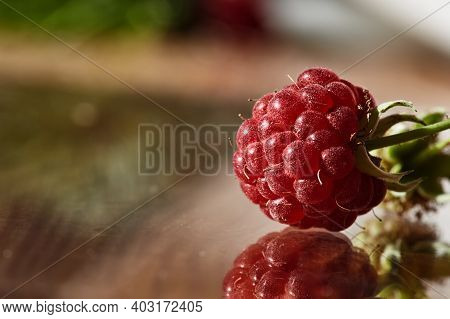 Red Raspberries On A Reflective Surface Glass. Fresh Raspberries On A Blurred Background.raspberry B
