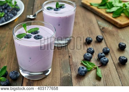 Blueberry Yogurt With Fresh Berries And Mint Leaves. Two Glasses Of Yogurt And A Lot Of Scattered Bl