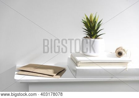 An Artificial Succulent Plant In A White Ceramic Vase Stands On Boxes And Notebooks. A Skein Of Craf