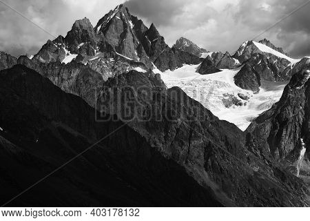 High Rocky Mountains With Glacier In Storm Clouds Before Rain. Caucasus Mountains. Georgia, Region S