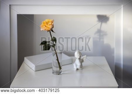 Orange Rose Of Candlelight In The Glass Vase And Angel Next To Fire Place Is Against Pale Grey Backg