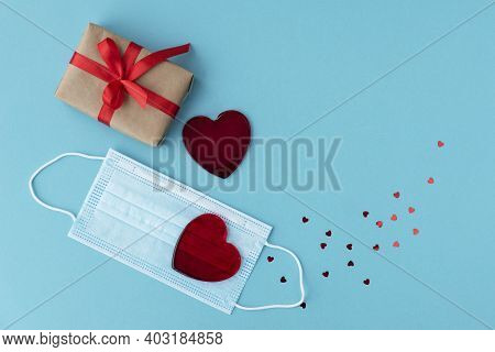 Red Hearts  Lie On Protective Medical Mask, Wrapped Giftbox And Little Sparkling Heart Confetti Are