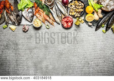 Fresh Seafood. Different Fish, Shrimp And Shellfish With Slices Of Lemon And . On A Stone Background