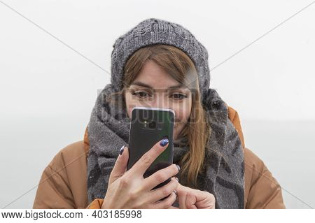 A Portrait Of A Girl In A Winter Hat And A Winter Jacket With A Scarf Holds A Smartphone And Takes A