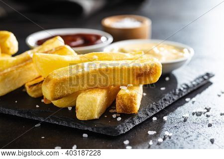 Big french fries. Fried potato chips on cutting board.
