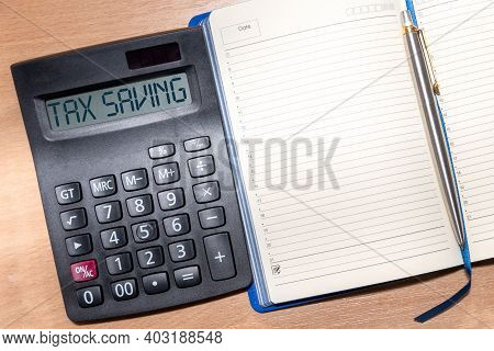 Calculator With The Text Tax Saving. Calculator, Notepad And Pen On A Wooden Table. Business, Financ