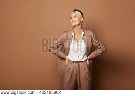 Fashion Studio Shot Of A Model Woman In A White Blouse And Beige Suit Isolated At The Beige Backgrou