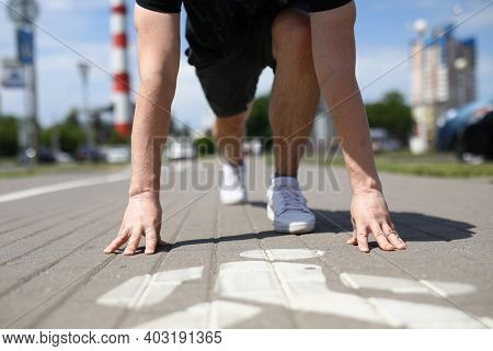 Close-up Of Male Person In Sports Uniform Beginning To Run From Low Start. Man Running On Sidewalk I