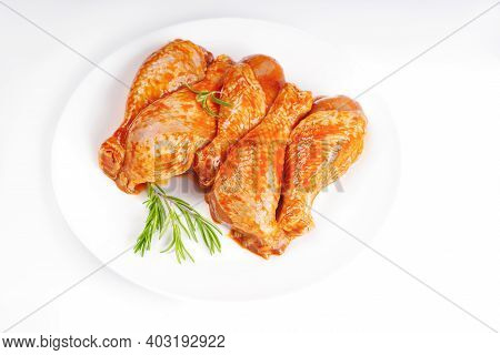 Raw Marinated Chicken Thighs For Grill And Bbq.uncooked Marinated Chicken Legs On A White Plate And