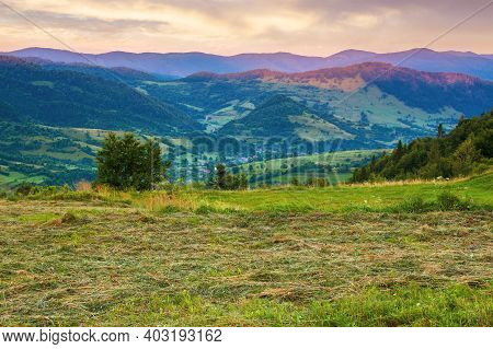 Mountainous Rural Landscape At Dawn. Grassy Meadow On Top Of A Hill. Clouds Above The Ridge. View In