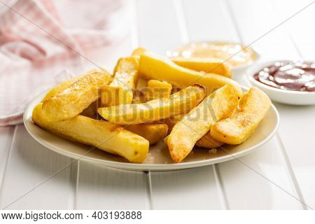Big french fries. Fried potato chips on plate.
