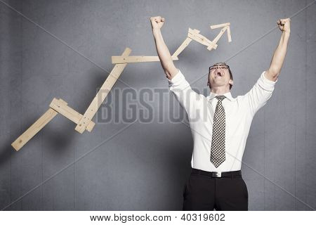 Concept: Success in business. Overjoyed talented businessman with raised arms cheering in front of positive business graph, isolated on grey background.