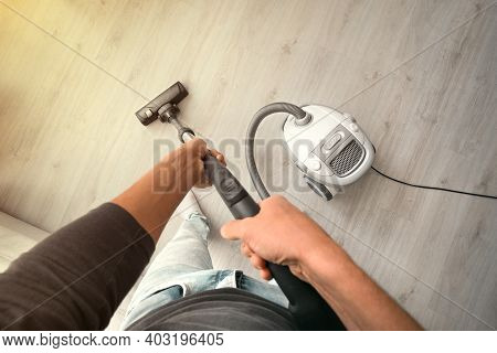 Man Using A Vacuum Cleaner At Home. Man Cleaning House. House Keeping. First-person View
