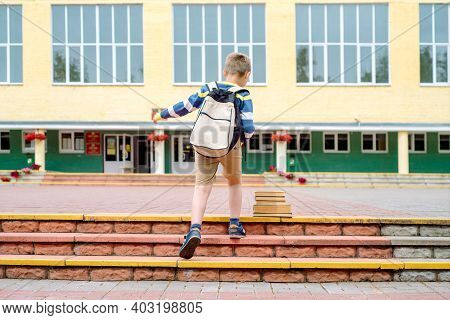 Portrait Of Schoolchild With Backpack Leaping . The Boy Runs A Backpack Around The School Yard.child