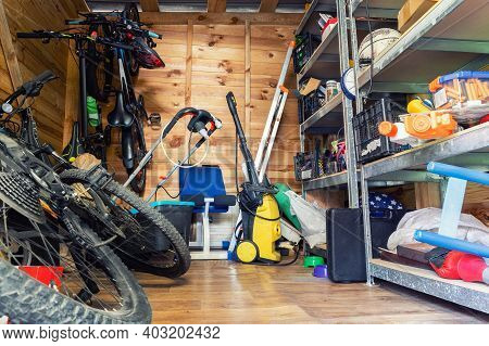 Suburban Home Wooden Storage Utility Unit Shed With Miscellaneous Stuff On Shelves, Bikes, Exercise