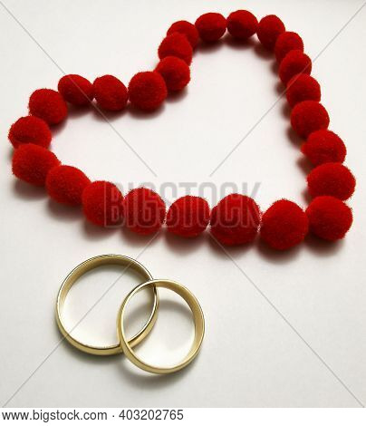 Gold Wedding Rings And Red Heart. Wedding Rings On The White Background, Surrounded By The Heart. Sy