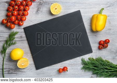 Vegetables And Blank Stone Frame On Wooden Table. Background For Food Recipe And Cooking Concept. To