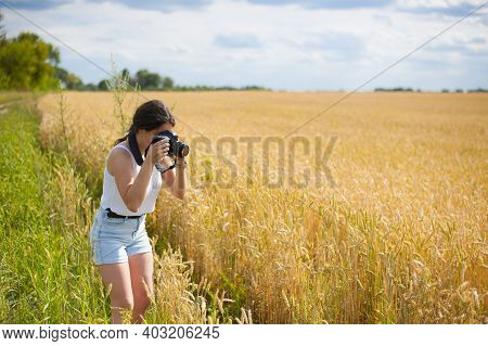 Young Woman In Nature. Girl Photographer Taking Photos With A Digital Camera. Girl With A Camera In