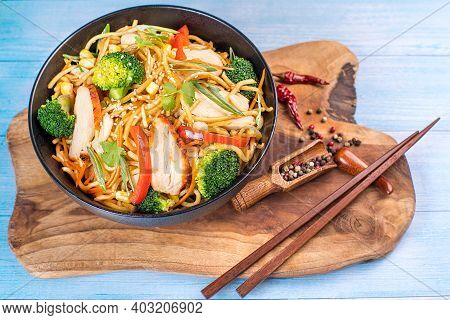 Chinese Noodles With Pieces Of Meat And Vegetables In A Black Bowl On The Kitchen Board. Noodles Wit