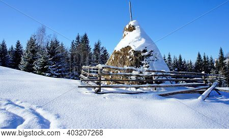 Snow-covered Haystack With A Wooden Fence And Clear Snow With Side Tracks On A Background Of Forest