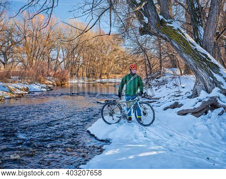 senior male cyclist with a touring bike on shore of the Poudre River in winter scenery,  recreation and commuting concept in Fort Collins, Colorado