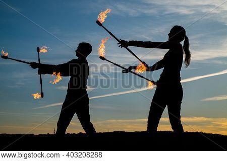 Energy Entertainment. Sexy Couple Manipulate Flaming Batons. Dark Shades On Idyllic Evening Sky. Fir