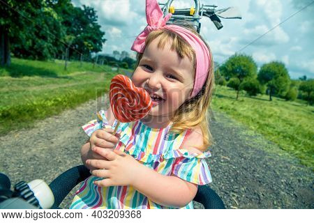 Fashionable Baby Girl, Sunglasses, Lollipop Like A Heart. Happy Children Hold Candy Green Grass Outd
