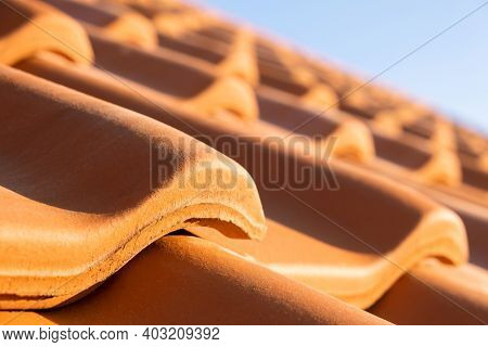 Overlapping Rows Of Yellow Ceramic Roofing Tiles Covering Residential Building Roof.