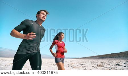 Athletes endurance training in extreme heat outdoors running in summer desert banner. Woman and man runners outdoor.