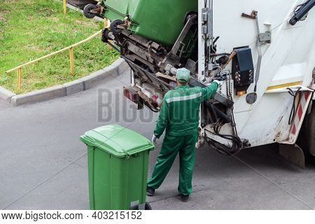 Garbage Collector Loads Garbage Truck With Household Waste From Garbage Cans