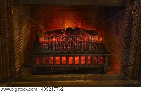 Glowing Electric Fireplace Log Heater In Fireplace With Open Fireplace Screen Curtains
