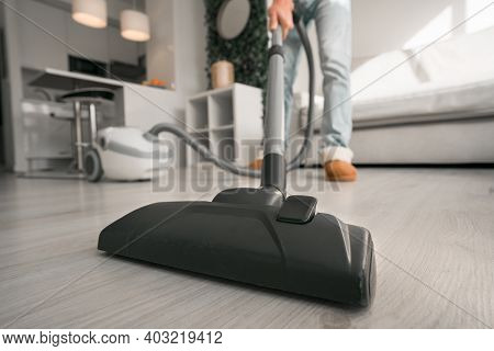 Man Cleaning Floor With Vacuum Cleaner At Home. House Keeping Concept. Close Up On Vacuum Cleaner