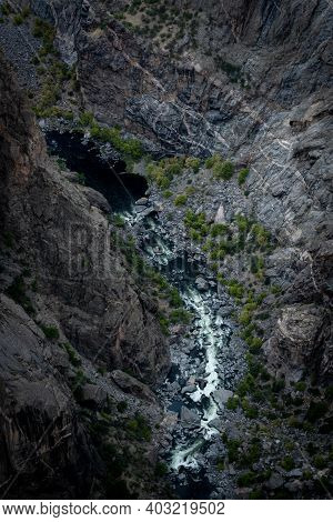 Dark Waters Of The Gunnison River Rush White In The Canyon Below The Rim