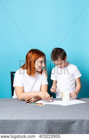 Mom And Son In White T-shirts Are Engaged In Drawing With Watercolors On A Blue Background. Learning