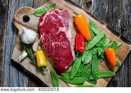 Beef rib club steak bonles on cutting board with vegetables