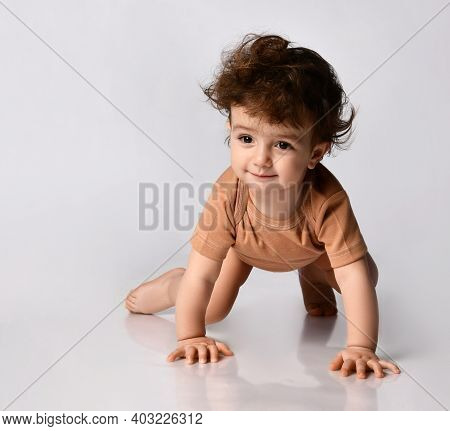 Charming Dark-haired Curly Baby Boy Crawls On All Fours On A Gray Background. Boy Looks With Interes