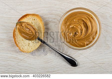 Metallic Spoon With Peanut Butter On Slice Of Bread, Transparent Glass Bowl With Peanut Butter On Wo