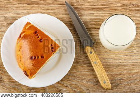Piece Of Pie With Cabbage And Egg In White Plate, Kitchen Knife, Glass Of Milk On Wooden Table. Top