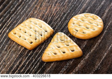 Cookies Triangular, Square And Round Shape On Dark Wooden Table