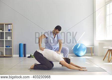 Man Doctor Osteopath Fixing Mans Back With Hands During Exersicing On Fitness Mat