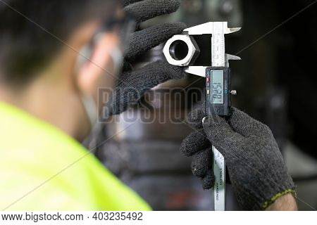 Closeup Behind Engineer Man Or Factory Worker Using Calipers Measures The External Dimension Of The