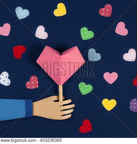 Hand Holding A Paper Origami Heart. Valentines Day Card, Paper Cutting. Flat Lay, Top View, Copy Spa