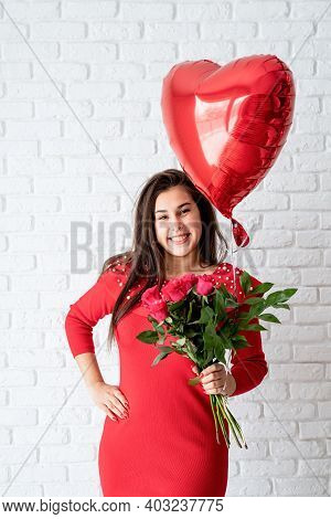 Young Brunette Woman In Red Dress Holding A Red Heart Balloon And Flowers