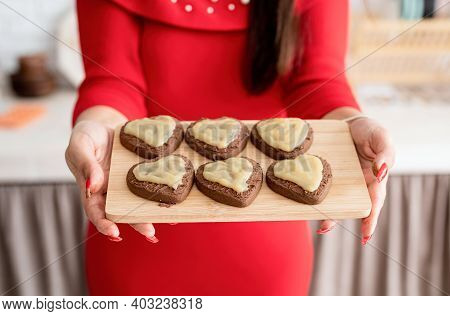 Woman In Red Dress Making Valentine Cookies At The Kitchen
