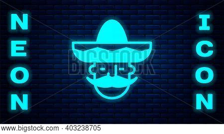 Glowing Neon Mexican Man Wearing Sombrero Icon Isolated On Brick Wall Background. Hispanic Man With