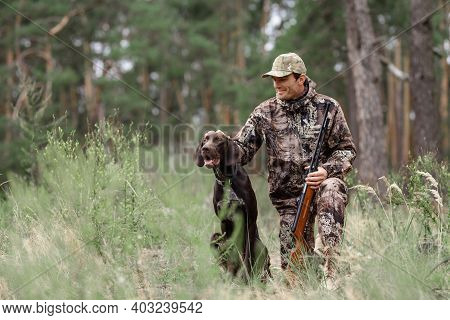 Happy Man With Rifle Hunter Pets Good Hunting Dog.