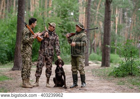Hunters Talking And Laughing Among Pine Trees.