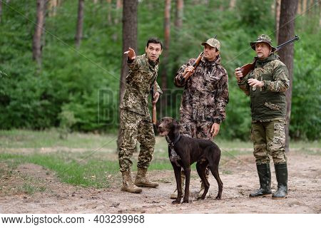 Group Of Hunters Pointing To Direction In Forest.